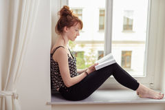 Pretty woman reading a book on a windowsill Royalty Free Stock Images