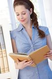 Pretty woman reading at bookshelf Royalty Free Stock Images