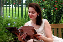 Pretty woman reading a colorful magazine Stock Photos