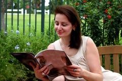 Pretty woman reading a colorful magazine