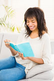 Pretty woman reading on couch Royalty Free Stock Images