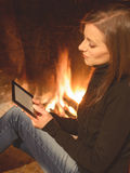 Pretty woman reading ebook sitting near the  hearth Royalty Free Stock Image