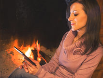 Pretty woman reading ebook sitting near the hearth Stock Photo