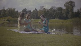 Pretty woman reading future with cards outdoors. Three attractive women reading future with tarot cards and guide book while sitting on picnic blanket on green stock video