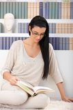 Pretty woman reading at home. Pretty woman sitting on floor reading book at home Stock Images