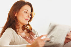 Pretty woman reading a newspaper Stock Image