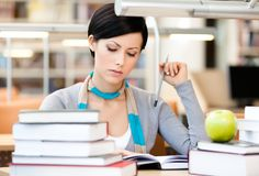 Pretty woman reads sitting at the desk. Woman with green apple surrounded with piles of books reads sitting at the table at the library. Educational process Stock Images