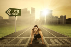 Pretty woman ready for lose weight. Portrait of a pretty woman with overweight body, preparing to run on the start line with text of lose weight on the signpost Stock Image