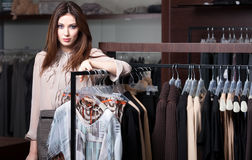 Pretty woman is in clothes shop Stock Image