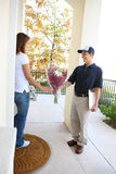 Pretty Woman Receiving Flowers. A delivery man giving flowers to pretty woman at home royalty free stock photography