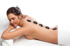 Pretty woman receiving a therapy with hot stones Stock Photography