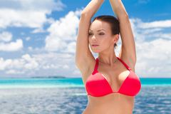 Pretty Woman in Red Bikini Top at the Beach. Pretty Young Woman in Red Bikini Top with Raised Arms at the Beach royalty free stock photography
