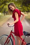 Pretty woman in red dress riding vintage bicycle. In park Stock Photos