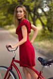 Pretty woman in red dress riding vintage bicycle. In park Royalty Free Stock Photo