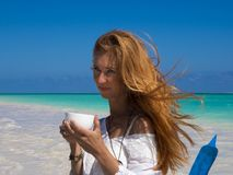 Pretty woman, red hair, at the boat, drinking tea on the beach royalty free stock photos
