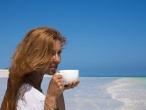 Pretty woman, red hair, at the boat, drinking tea on the beach royalty free stock image