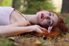 Pretty woman with red hair in jersey lies on dry foliage Stock Image