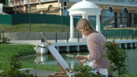 A pretty woman with red hair, paints a picture on canvas, which stands on the easel. The lady is in the open air near. The lake of the river, she draws from stock footage