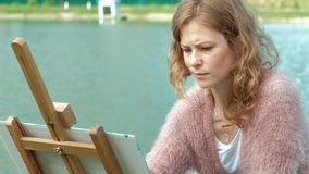A pretty woman with red hair, paints a picture on canvas, which stands on the easel. The lady is in the open air near. The lake of the river, she draws from stock video