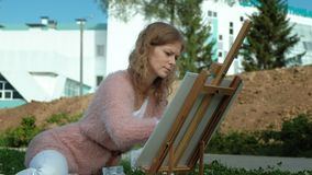 A pretty woman with red hair, paints a picture on canvas, which stands on the easel. The lady is in the open air near stock video