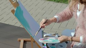 A pretty woman with red hair, paints a picture on canvas, which stands on the easel. The lady is in the open air near stock video footage
