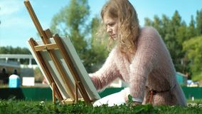 A pretty woman with red hair, paints a picture on canvas, which stands on the easel. The lady is in the open air near stock footage