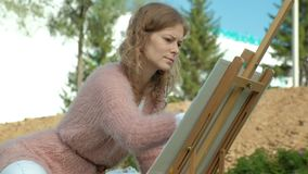 A pretty woman with red hair, paints a picture on canvas, which stands on the easel. The lady is in the open air near. The lake of the river, she draws from stock video footage