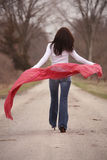 Pretty Woman in Red Shawl. Pretty young brunette woman walking away with red shawl Stock Images