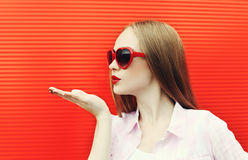 Pretty woman in red sunglasses sends an air kiss Royalty Free Stock Images