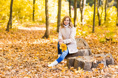 Pretty woman relaxing in the autumn park Royalty Free Stock Photography