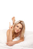 Pretty woman relaxing in bed pointing a finger Stock Images