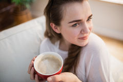Pretty woman relaxing on couch with coffee. In the living room Royalty Free Stock Photography