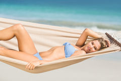 Pretty woman relaxing in the hammock and smiling at camera Royalty Free Stock Images
