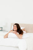 Pretty woman relaxing at home lying on her bed. With a pillow Royalty Free Stock Image