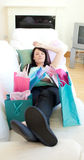 Pretty woman relaxing after shopping. Pretty woman relaxing on her sofa after shopping Royalty Free Stock Photos