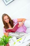 Pretty woman relaxing on sofa and reading book Stock Photography