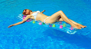 Pretty woman relaxing in swimming pool. Royalty Free Stock Photo
