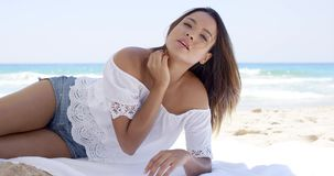 Pretty woman relaxing under a beach umbrella. Pretty woman in summer shorts and blouse relaxing under a beach umbrella on a tropical beach looking thoughtfully stock footage