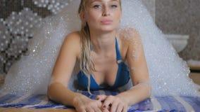 Pretty woman relaxing under the bubbles foam in the Turkish bath stock video