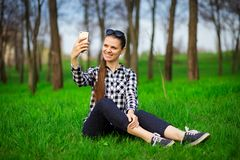 Pretty woman resting in park and take selfie on phone. Concept of communication and leisure time stock photo