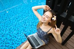 Happy woman rest after hard work at swimming pool with laptop, d stock photography