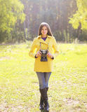 Pretty woman with retro camera in sunny Stock Photos