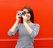 Pretty woman with retro vintage camera in city over red Stock Photo