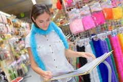 Pretty woman reviewing costumes on collection magazine at shop stock photography