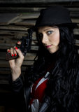Pretty woman with revolver and leather jacket Stock Photography