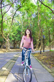 Pretty Woman riding a bike on the forest trail Stock Images