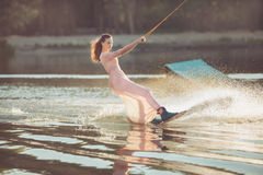 Pretty woman riding a wakeboard. Pretty woman riding a wakeboard on the lake in the park Royalty Free Stock Image