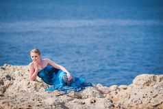 Pretty woman on the rocky mountain near the sea Royalty Free Stock Image