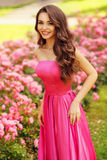 Pretty woman in roses buches Stock Photography