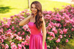 Pretty woman in roses buches Royalty Free Stock Images